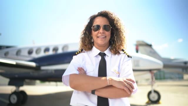 porträtt av flygplan pilot framför en privat jet och titta på kamera - pilot bildbanksvideor och videomaterial från bakom kulisserna