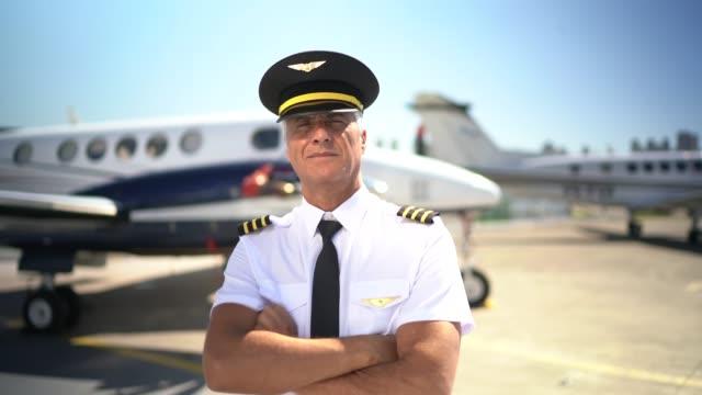 özel bir jet önünde uçak pilotu portresi ve kamera bakıyor - üniforma stok videoları ve detay görüntü çekimi