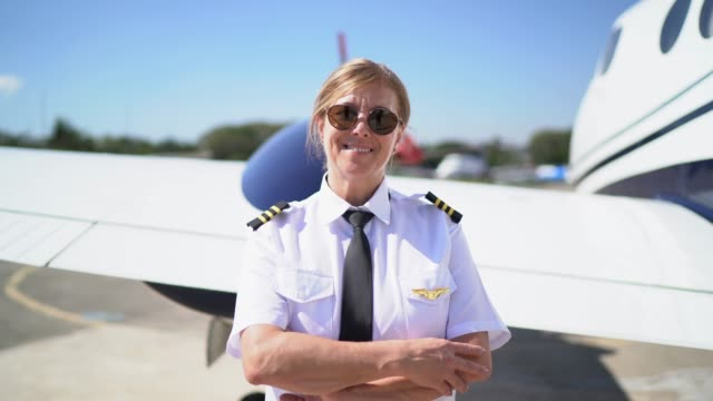 Portrait of airplane pilot in front of a private jet and looking at camera