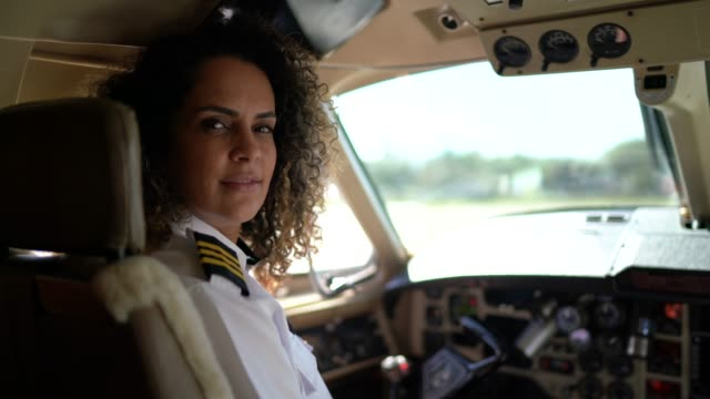 Portrait of airplane pilot looking over shoulder in a private jet Portrait of airplane pilot looking over shoulder in a private jet businesswear stock videos & royalty-free footage