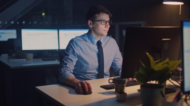 야심 차고 자신감 사업가의 초상화는 데스크톱 컴퓨터를 사용 하 여 키보드에 입력, 비즈니스 거래를 모니터링, 계약에 서명. 큰 회사 사무실에서 밤 늦게 작동 - 헌신 스톡 비디오 및 b-롤 화면