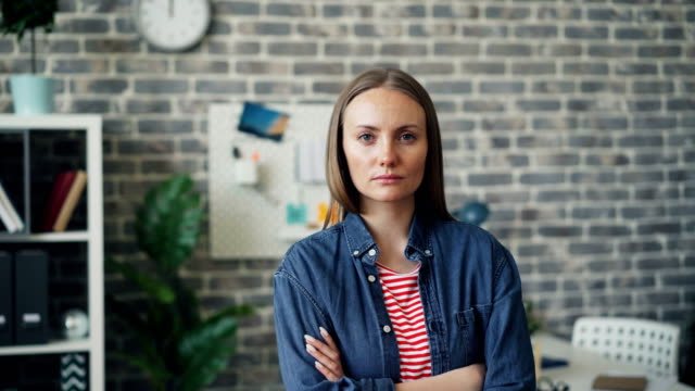 Portrait of ambitious independent woman standing in office with arms crossed