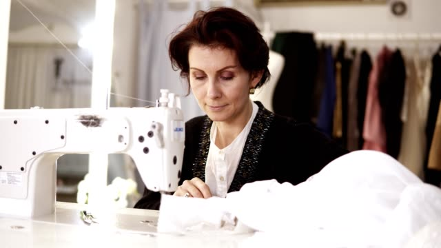 Portrait of an adult woman seamstress works at a sewing machine, working on a white hand made dress. Fashion clothes on the background in tailor's studio. Woman working on a wedding dress video