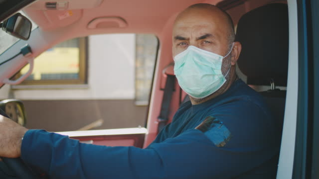 slo mo portrait of an ambulance driver putting on a medical mask - mask стоковые видео и кадры b-roll