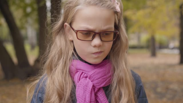 stockvideo's en b-roll-footage met portret van een boze kaukasische tiener meisje staande in de herfst park en kijken naar de camera. jonge schoolmeisje in meekleurende bril en roze sjaal ontevreden met haar vrije tijd buitenshuis. - blond curly hair