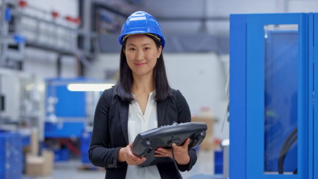 DS Portrait of an Asian female engineer holding the control panel for the machine in the background Wide dolly shot of an Asian female engineer wearing a hard hat and holding a control panel for the machine in the factory while looking into the camera and smiling. Shot in Slovenia. occupational safety and health stock videos & royalty-free footage