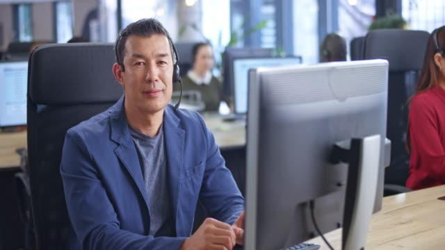 彼のワークステーションでカメラに微笑むアジアの男性コールセンターエージェントの肖像画 - 上半身点の映像素材/bロール