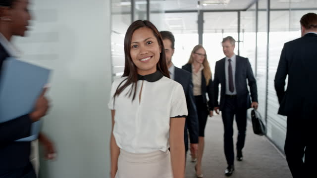 Portrait of an Asian office employee walking in the office hallway, ending the phone call and smiling into the camera video