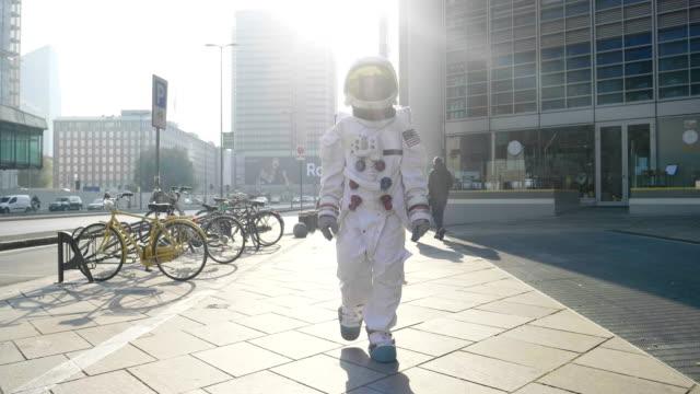 vídeos de stock, filmes e b-roll de retrato de um astronauta que acaba de desembarcar e andar pela primeira vez em cidade e de olhares ao redor no metrô e no ar livre na cidade. conceito de: liberdade, novos planetas, ambição, exploração, surreal - surreal