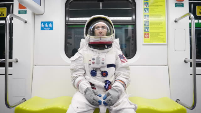portrait of an astronaut just landed and walking for the first time in town and looks around in both the metro and open air in the city. concept of: freedom, ambition, new planets, exploration,surreal - sognare video stock e b–roll