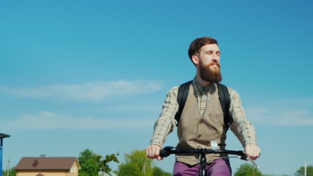 Portrait of an attractive bearded man. Riding a bicycle, in the background a beautiful blue sky - a clear spring day video