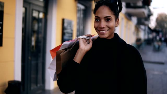 Portrait of an attractive mixed race girl smiling while walking down the street with colorful shopping bags. Happy young woman walking after shopping by fancy streets city, window shopping