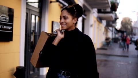 porträt eines attraktiven gemischten rennmädchens lächelnd, während er mit einer kleinen braunen tasche die straße entlanggeht. glückliche junge frau zu fuß nach dem einkaufen durch ausgefallene straßen stadt - eleganz stock-videos und b-roll-filmmaterial