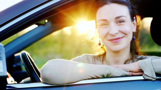 Portrait d'une jeune femme séduisante dans la voiture. Souriant, en regardant la caméra à travers la fenêtre ouverte, après le coucher du soleil. Est assis à la place du conducteur - Vidéo