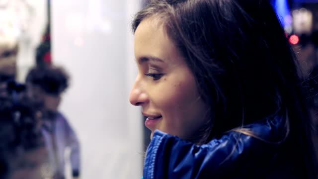 stockvideo's en b-roll-footage met portret van een aantrekkelijke jonge vrouw die kijken naar de etalage - raam bezoek