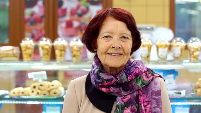 Portrait of an elderly grandmother in a grocery store in the Department of bread