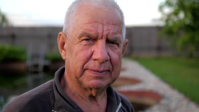 vidéos et rushes de portrait d'un vieil homme, les cheveux gris et les rides profondes, se penche sur la caméra. - abaisser