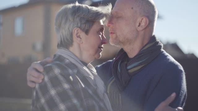 stockvideo's en b-roll-footage met portret van een omarmen volwassen echtpaar staande in de koele winderige zonnig weer. - bewondering