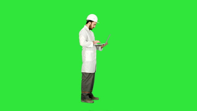 portrait of an engineer in helmet using a laptop on a green screen, chroma key - craftsman architecture stock videos & royalty-free footage