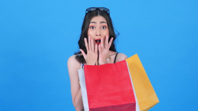 Portrait of an excited and smiling young asian woman with shopping bags.Women are shopping in the summer and enjoys shopping bags isolated on over blue background.Consumerism, shopping, lifestyle concept