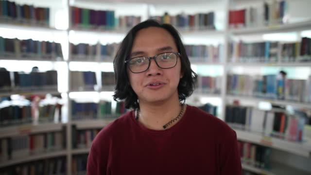 portret malajskiego mężczyzny uśmiechniętego w szkolnej bibliotece - portret do pasa filmów i materiałów b-roll
