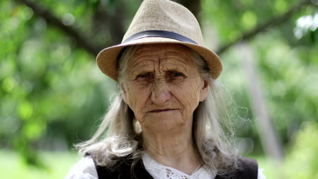 Portrait of an old woman with long gray hair in a straw hat outdoors. video