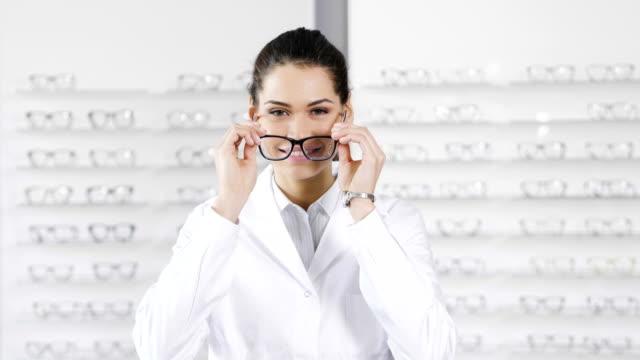 porträt der augenarzt eine sichtprüfung zu tun, für einen kunden in einen optischen mittelpunkt. - augenoptiker stock-videos und b-roll-filmmaterial