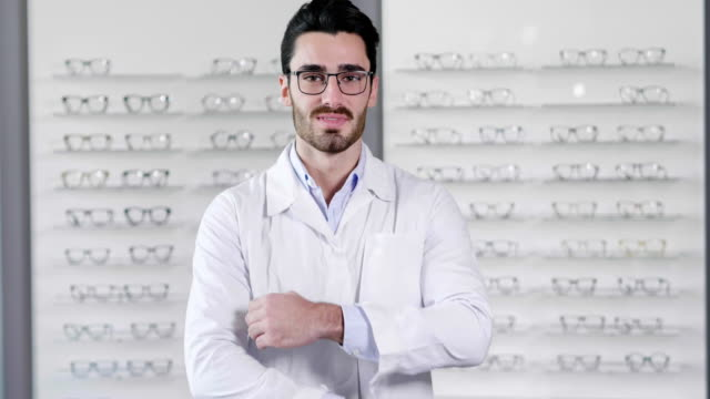 porträt der augenarzt eine sichtprüfung zu tun, für einen kunden in einen optischen mittelpunkt. versuchen sie die brille für den patienten. - augenoptiker stock-videos und b-roll-filmmaterial