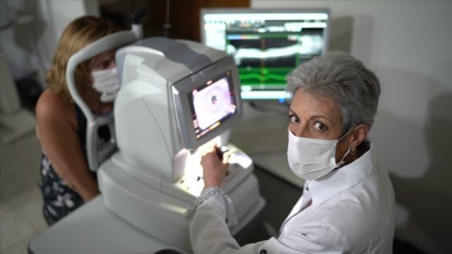 porträtt av en ögonläkare gör en synundersökning - optiska instrument bildbanksvideor och videomaterial från bakom kulisserna