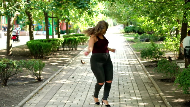 Portrait of an overweight girl in Park in summer. A young happy girl with excess weight walks in a summer park, she swims around herself and enjoys warm weather. Plus size model. large stock videos & royalty-free footage