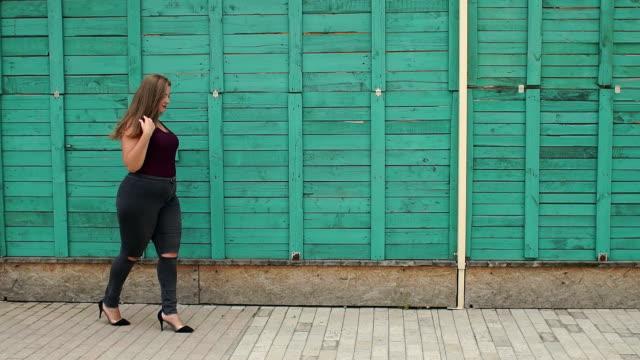 porträtt av en överviktig tjej med långt hår i parken. - jeans bildbanksvideor och videomaterial från bakom kulisserna