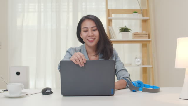 Portrait of Asia freelance smart business women casual wear using laptop working in living room at home. Portrait of Asia freelance smart business women casual wear using laptop working in workplace in living room at home. Happy young Asian girl relax sitting on desk search and do job in internet. asia stock videos & royalty-free footage