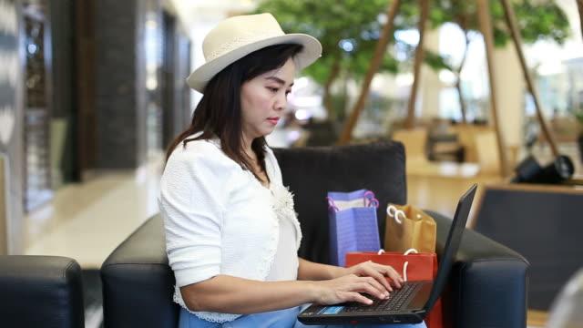 portrait of asian businesswoman using laptop - owner laptop smartphone video stock e b–roll