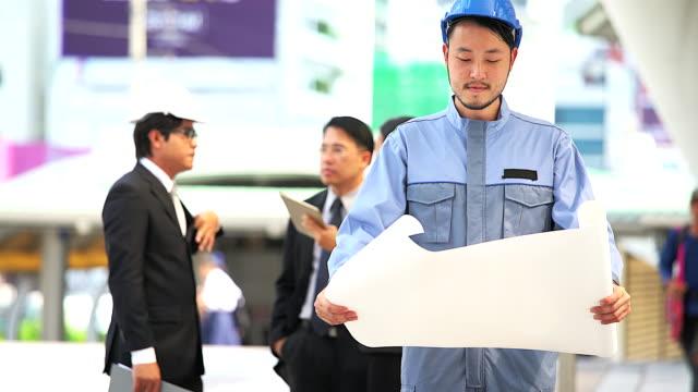 Porträt des asiatischen Ingenieur mit Bauplan mit Gruppe von Geschäftsleuten, die Treffen in den Hintergrund. – Video