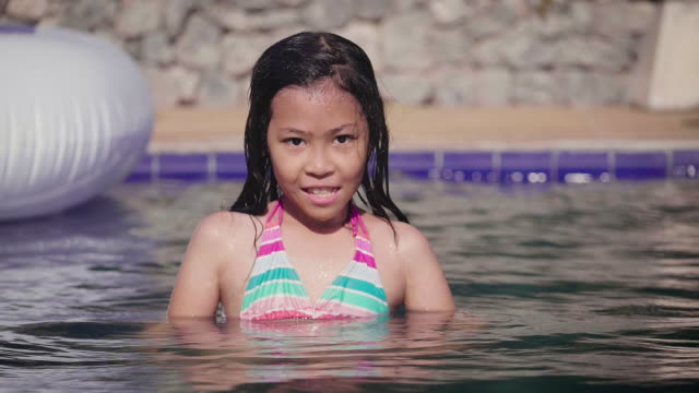 Portrait of Asian girl having fun and relaxing in swimming pool, Summer vacation concept