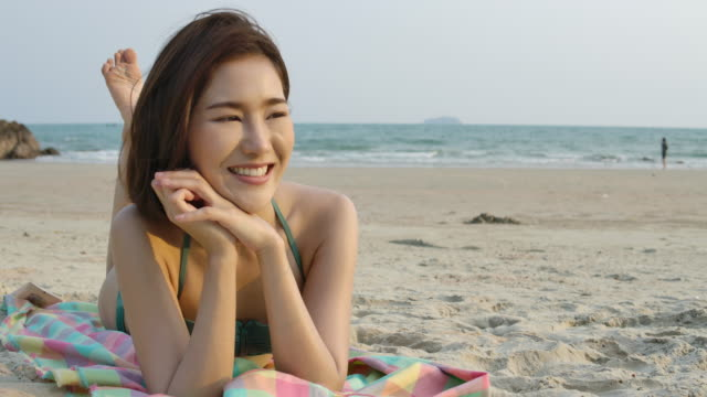 Portrait of asian girls in bikini lying on sand at the beach and looking at camera. Beautiful asian girl during summer vacation. celebration and relaxation concept.