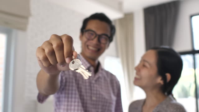 portrait of asian happy couple standing in new home with keys - key ring stock videos & royalty-free footage