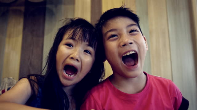 Portrait of asian kids, happy asian boy and girl looking at camera and smiling. Sequence video
