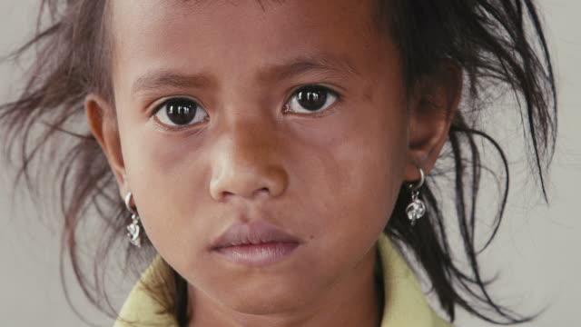 vídeos y material grabado en eventos de stock de retrato de niña asiática, hembra niño mirando a la cámara - estilo de vida austero
