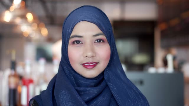 portrait of asian muslim woman look at camera and smile. - islam filmów i materiałów b-roll