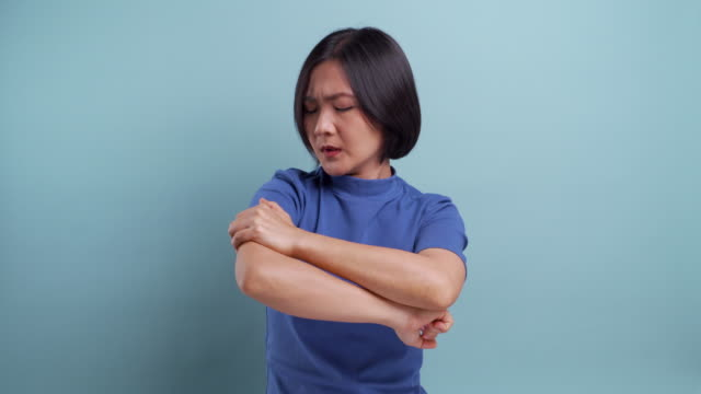 Portrait of asian woman has body pain isolated on blue background. 4K video Portrait of asian woman has body pain isolated on blue background. 4K video arm stock videos & royalty-free footage