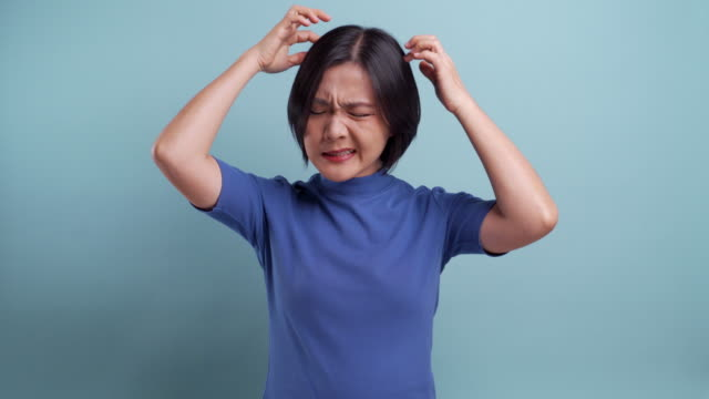 Portrait of asian woman scratching her head isolated on blue background. 4K video