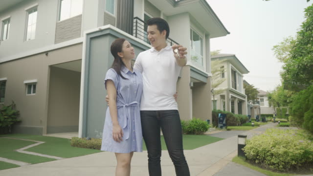 vídeos de stock e filmes b-roll de portrait of asian young couple standing and hugging together and holding house key looking happy in front of their new house to start new life. family, age, home, real estate and people concept. - buy a house key