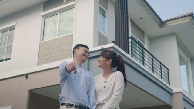 porträt eines asiatischen jungen paares, das zusammensteht und sich umarmt und den hausschlüssel hält, der glücklich vor ihrem neuen haus aussieht, um ein neues leben zu beginnen. familien-, alters-, wohn-, immobilien- und menschenkonzept. - hausschlüssel stock-videos und b-roll-filmmaterial
