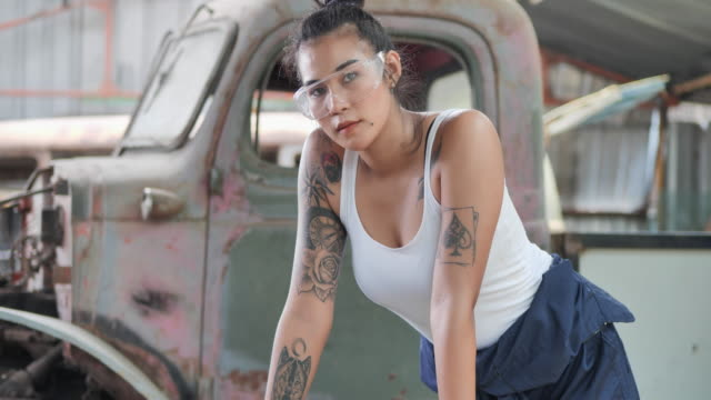 Portrait of asian young female having tattooes on arms, she's welder smile and looking at camera.