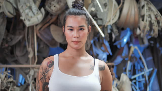Portrait of asian young female having tattooes on arms, she's welder smile and looking at camera.Women in Blue Collar Jobs concept.