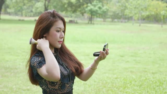 портрет азиатской молодой женщины, применяя косметический порошок на ее лице, концепция макияжа лица красоты. - white background стоковые видео и кадры b-roll