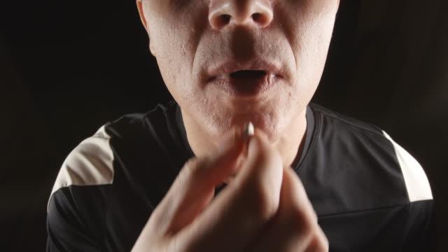 doping: atlet portre soyunma odasında ağzına bir hap alır - doping stok videoları ve detay görüntü çekimi