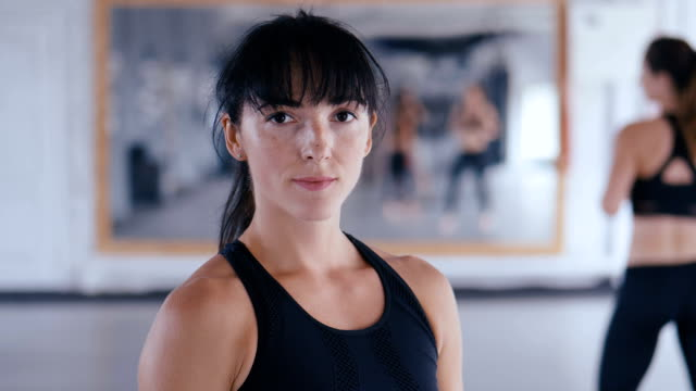portrait of athletic woman looking confident at camera in gym. attractive sportswoman after training in fitness gym close-up. - kick boxing video stock e b–roll