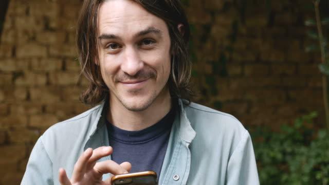 スマートを使用して魅力的な 20 〜 30 歳の男性の肖像画携帯電話 - ドリー ビデオ